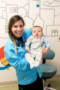 Dr. Lisa Bienstock holding a child